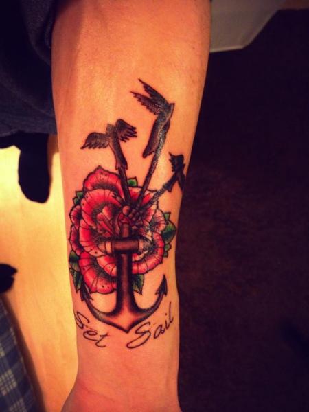 Ein Anker mit Schwalben und eine Rose im Hintergrund