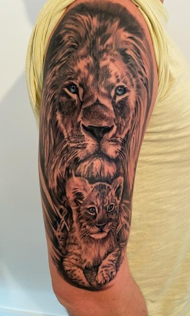 Löwe mit Löwenbaby auf Oberarm