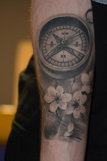 kompass-Tattoo: Kompass mit Kirschblüten auf Tischplatte